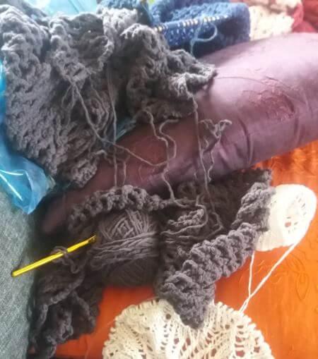 Massor av garn, stickningar och virkningar i soffan.