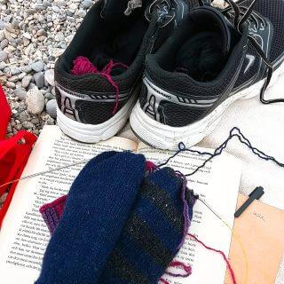 Visst kan du sticka ullstrumpor på stranden. Och läsa bok, samtidigt!