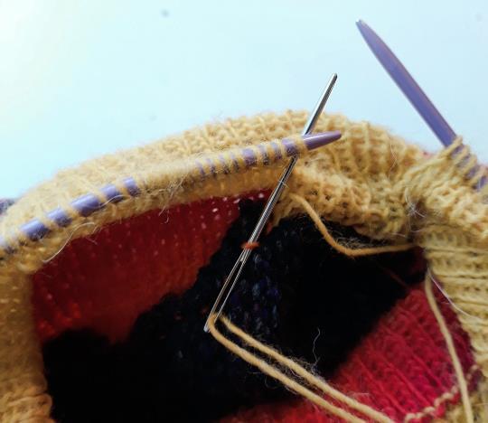 Sticka dubbel halskant: sy fast maskorna från stickan med kaststygn i maskorna som du plockade upp längs halsringningen.