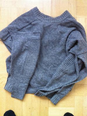 Genom hela ponchon löper det ljusgrå ull/lin-garnet från en begagnad herrtröja.